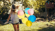 Girl playing outdoors with balloons
