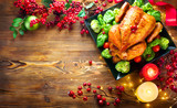 Christmas dinner. Roasted chicken on holiday table, decorated with berries, candles and garlands. Roasted turkey over wooden background. Top view, flatlay - 236601334