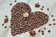 Heart of coffee beans with star of anise and satin in pastel shades of a rose on a light wooden background.