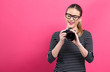 Leinwanddruck Bild - Young woman with a professional digital SLR camera on a pink background