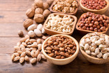 bowls of nuts on wooden table - 236607308
