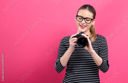 Leinwanddruck Bild Young woman with a professional digital SLR camera on a pink background