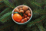 small bowl with nuts and a satsuma on spruce branches