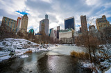 Stark urban winter scene of the Midtown Manhattan skyline towering above a wintry landscape view of the Central Park Pond after a snow storm in New York City