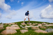 Young man in sportswear walking down big stones on green field as part of his morning workout