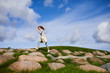 Active young woman walking down large stones against cloudy sky in the morning