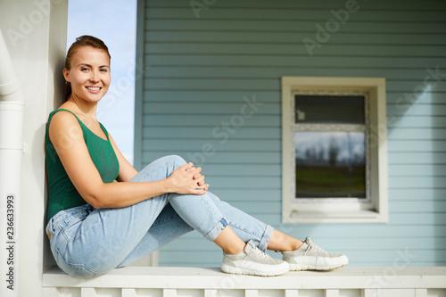Młoda uśmiechnięta kobieta w casualwear obsiadaniu na tarasie nowy dom i patrzeć ciebie