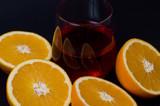 glass of juice and orange on black background