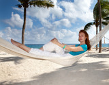 beautiful young woman in a hammock on the beach on background of palm trees and the sea..