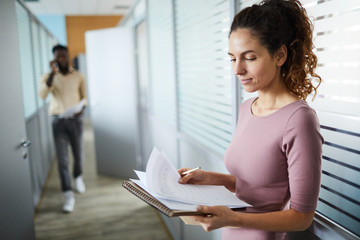 Young businesswoman standing in corridor by office and looking through financial papers