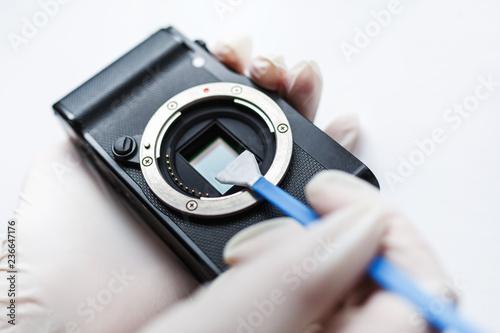 Leinwandbild Motiv Close-up of mirrorless digital APS-C dirty camera matrix sensor cleaning and maintenance with swab, photographer cleaning photocamera on white background