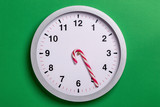 Christmas clock with candy cane hands shows five o'clock - 236650760