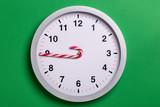 Christmas clock with candy cane hands shows nine o'clock
