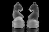 Two glass chess pieces on a black background