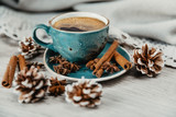 turquoise cup of hot coffee with cinnamon sticks on grey background