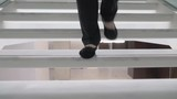 A steadicam shot of female feet going downstairs. A woman is wearing black pants and black shoes with sparkly details. Steps beneath her feet are white and glossy - 236683564