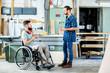 Leinwanddruck Bild - worker in wheelchair in a carpenter's workshop with his colleague in conversation