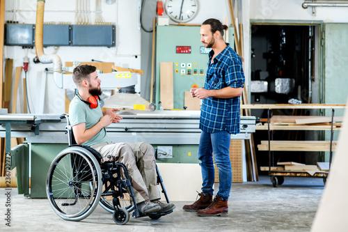 Leinwanddruck Bild worker in wheelchair in a carpenter's workshop with his colleague in conversation