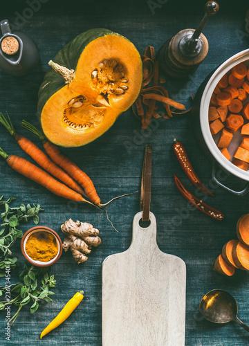 Pomarańczowy kolor gotowania składników wokół deski do krojenia. Dynia, marchew, słodkie ziemniaki, kurkuma, chili i świeże przyprawy do zdrowej wegetariańskiej zupy lub gulaszu na zimno, widok z góry
