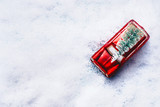 Top view of on red toy retro car with green Christmas tree in snow. Creative Christmas holiday concept. Copy space for your design. Festive greeting card