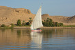Traditional egyptian felluca sailing boat on river Nile with reflection at Aswan