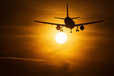 Silhouette of an air plane near to the sun with beautiful red clouds in background - 236744388