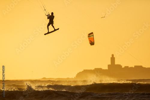 fototapeta na ścianę Silhoutte of kitesurfers enjoying big waves at sunset in Essaouira, Morocco. Beautiful landscape in background