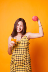 Young Asian woman with dumbbell drink orange juice. © halfbottle