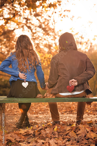 Leinwanddruck Bild Couple in autumn season colored park enjoying outdoors.