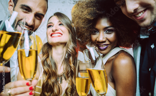 Men and women celebrating birthday or new years party while clinking glasses with sparkling wine - 236751928