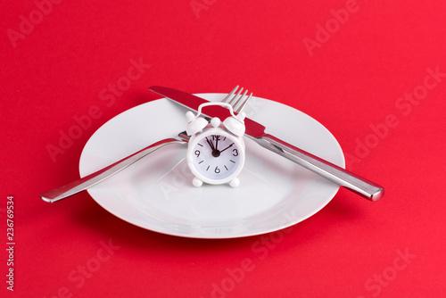 fototapeta na ścianę Uhr mit einem Teller und Besteck beim Essen
