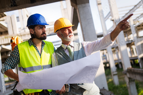 Fototapeta Team of architects and engineer in group on construciton site check documents and business workflow
