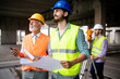 Leinwanddruck Bild - Engineer and construction site manager dealing with blueprints and plans