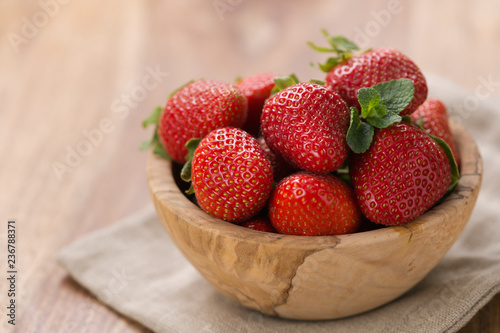 Ripe strawberries in wooden bowl on wood background with copy space - 236788371