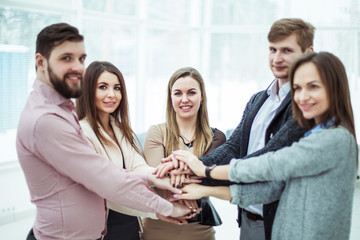 concept of teamwork:friendly business team standing in a circle, hands clasped together