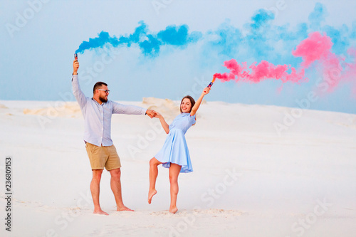 young couple standing on a sand and holding colored smoke bomb