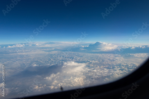 Blue sky in the porthole, white fluffy clouds below. Blue horizon, view from the airplane's porthole. The plane flies over the white clouds. - 236809379