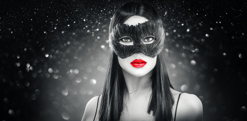 Beauty glamour brunette woman wearing carnival feather dark mask, party over holiday glowing black background