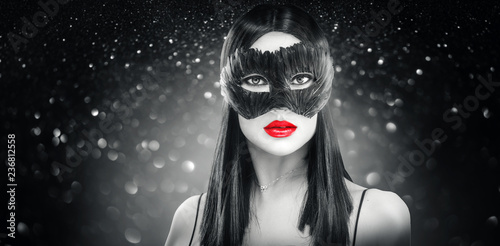Beauty glamour brunette woman wearing carnival feather dark mask, party over holiday glowing black background - 236812558