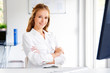 Attractive young businesswoman sitting at office desk in front of computer
