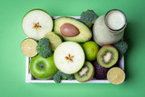 Smothie bottle and green fruits in a tray. Kitchen table above view - 236834720