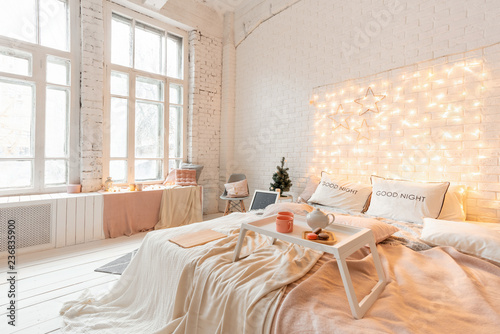 Leinwandbild Motiv Christmas morning, Breakfast in bed, coffee and desserts. Loft style apartments. Bed in the bedroom, high large Windows. Brick wall with candles and Christmas tree. White color.