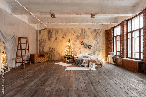 Leinwandbild Motiv Loft style apartments. Bed in the bedroom, high large Windows. Brick wall with candles and Christmas tree. warm and brown color