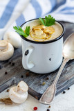 Cream-soup with champignons in an enamel mug. - 236838740