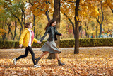 Two happy girls running in autumn city park. - 236842349