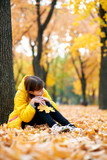 Sad teen girl sits near tree in autumn park. Bright yellow leaves and trees. - 236842547