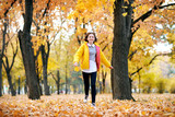 Happy teen girl is running in autumn park with big maple's leaf. Bright yellow leaves and trees. - 236842594