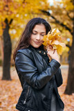Pretty woman is posing with bunch of maple's leaves in autumn park. She's closing eyes and dreaming. Beautiful landscape at fall season. - 236842750