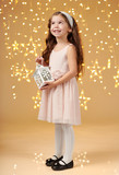 girl child is posing with lantern in christmas lights, yellow background, pink dress - 236842960