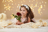 girl child with rose flower is posing in christmas lights, yellow background, pink dress